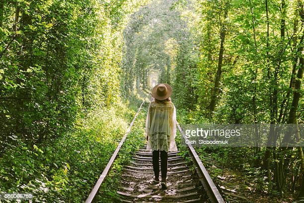 girl walking in tree tunnel - ウクライナ トンネル ストックフォトと画像