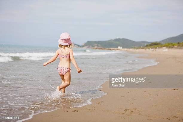 Girl walking in waves on beach