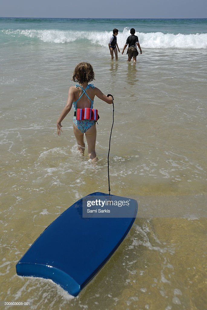 Girl (5-7) walking into surf, pulling float, rear view : Stock Photo