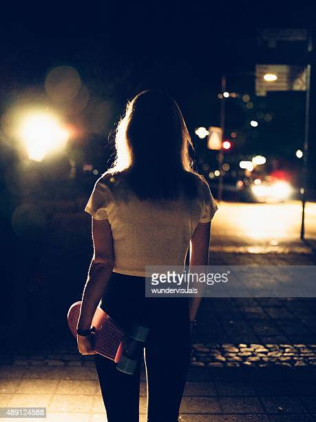 Girl walking on a street at night carrying her skateboard