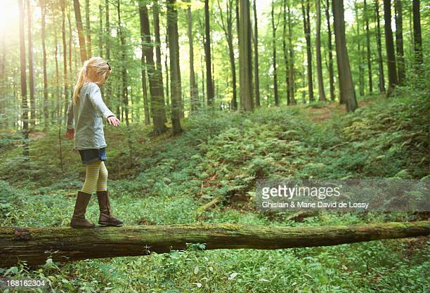 girl walking on a tree trunk - nature stock pictures, royalty-free photos & images