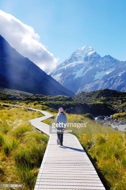 girl walking on boardwalk at hooker valley track, with view of mount cook - região de canterbury nova zelândia - fotografias e filmes do acervo