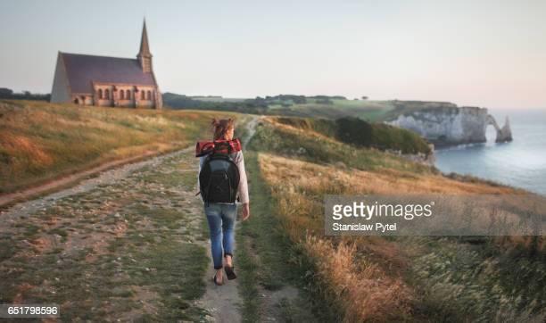 Girl walking on cliff at sunset