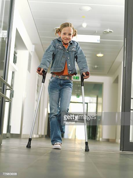 girl (7-10) walking on crutches in hospital hall, low angle view - crutch stock photos and pictures