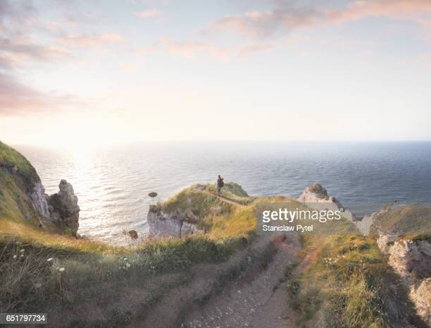 Girl walking on edge of grassy cliff