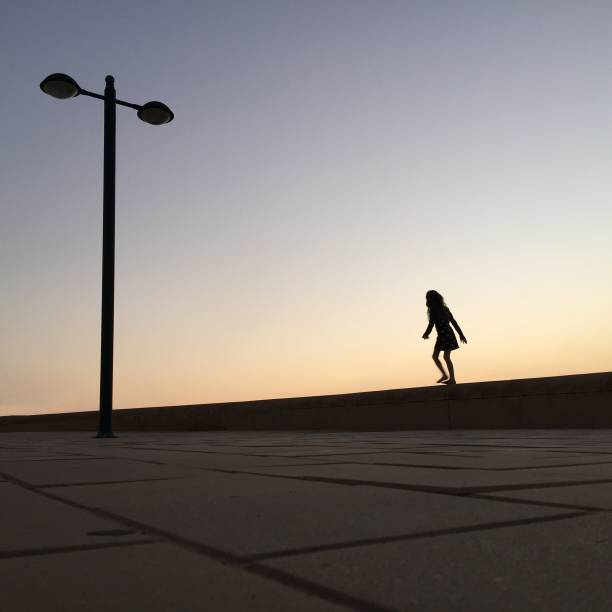 Girl Walking On Retaining Wall Against Sky During Sunset