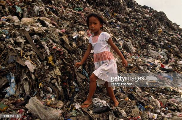 Girl walking on rubbish in landfill site, Philippines
