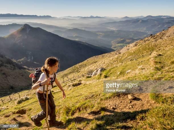 Girl walking on single trail towards hill