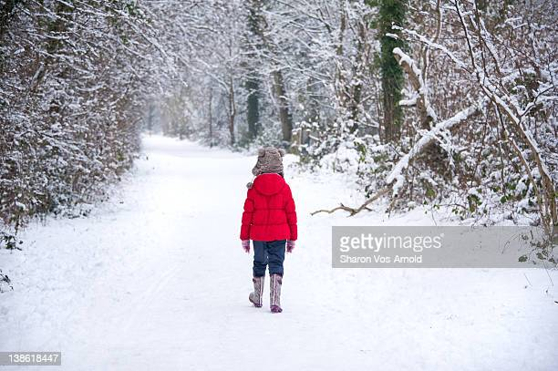 girl walking on snow - red jacket stock pictures, royalty-free photos & images
