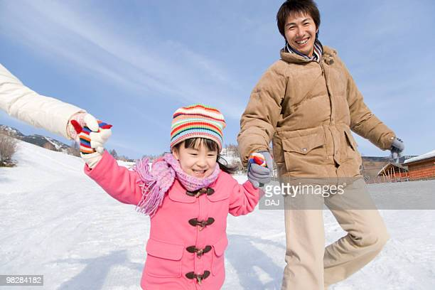 Girl walking on snow with parents, hand in hand, smiling