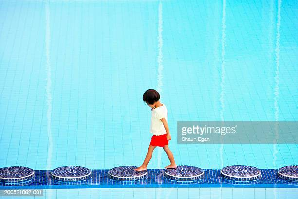 Girl (2-4) walking on stepping stones in swimming pool