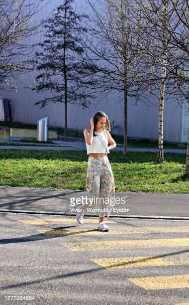 girl walking on street listening to musik - musik stock pictures, royalty-free photos & images