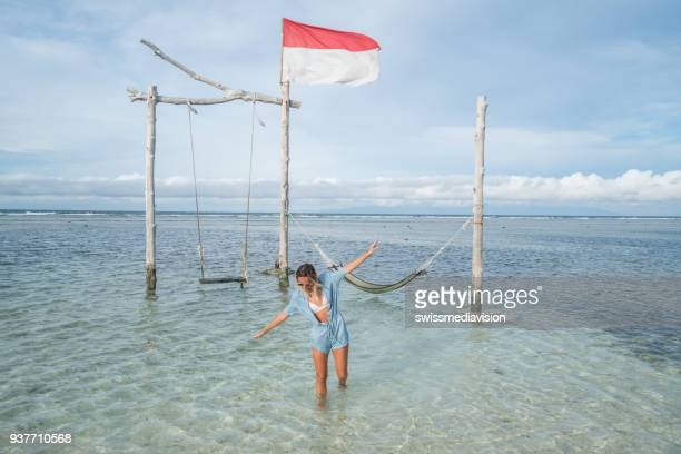 girl walking on the beach, swing by the sea, indonesia - indonesia flag stock photos and pictures