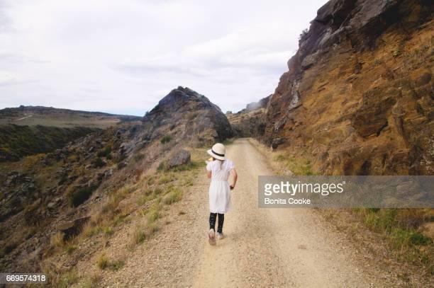 Girl walking on the Central Otago rail trail, carved through schist rock bluffs in Poolburn Gorge, Lauder