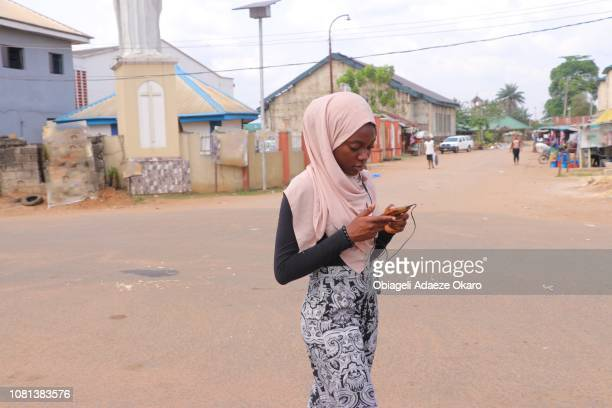 a girl walking on the streets of her community - nigeria stock pictures, royalty-free photos & images