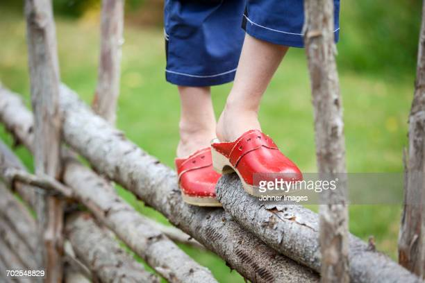 Girl walking on wooden fence, low section