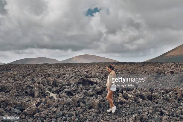 girl walking over lava in lanzarote - timanfaya national park stock pictures, royalty-free photos & images