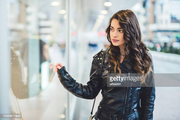 girl walking the city and looking at shop windows. - black jacket stock pictures, royalty-free photos & images