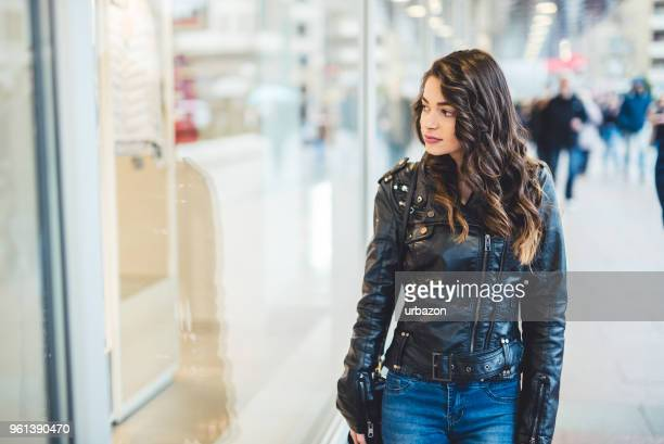girl walking the city and looking at shop windows. - giacca di pelle foto e immagini stock