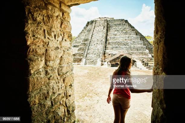 girl walking through doorway while exploring mayapan ruins during vacation - archaeology stock pictures, royalty-free photos & images