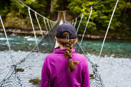 Girl walking through hanging bridge - gettyimageskorea