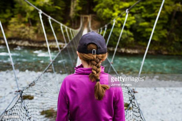 Girl walking through hanging bridge
