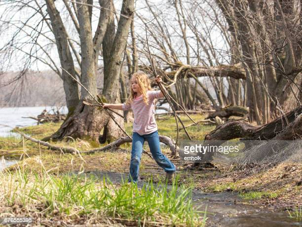 girl walking through woods on riverbank in early springtime - handful stock pictures, royalty-free photos & images
