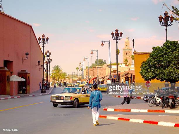 Girl walking to the medina, it is posiible to see the miranet of Koutoubia mosque in the bachground, whilst a taxi is turning in the road.
