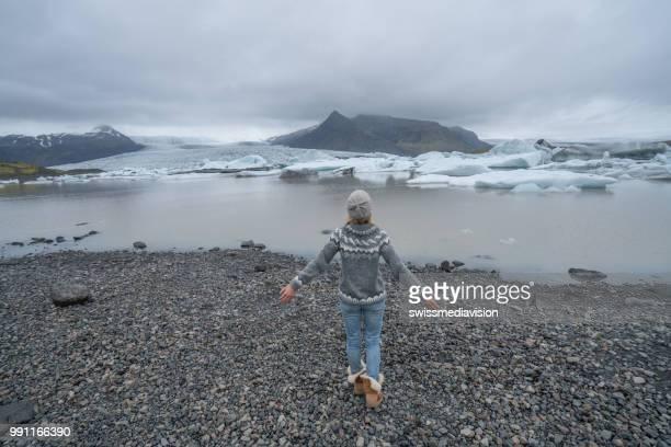 Girl walking towards glacier lake in Iceland, spectacular ice landscape