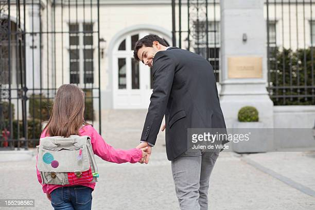 Girl walking towards school with her father