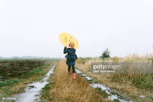 Girl walking under the rain on field