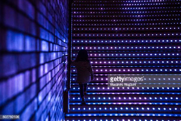 A girl walking up the steps with illumination