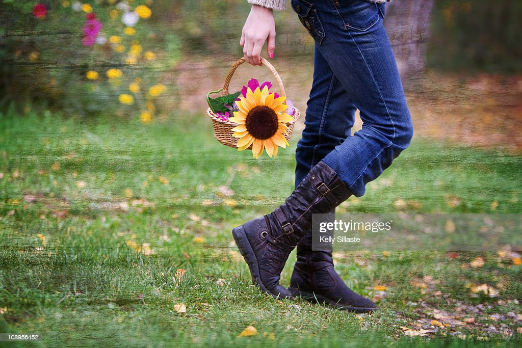 A girl walking with a basket of flowers : Stock Photo
