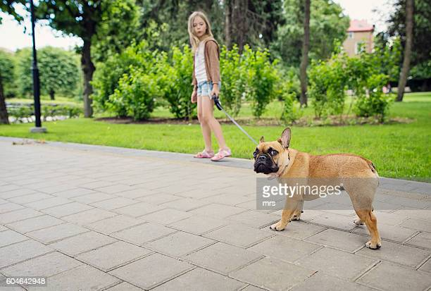 Girl walking with a dog in the park