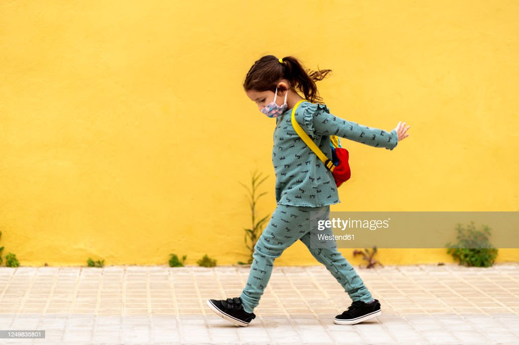girl walking with backpack and mask outdoors : Stock Photo