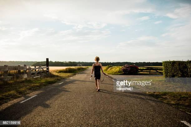 girl walking with dog on rural road holding miniature wind turbine - friesland noord holland stockfoto's en -beelden