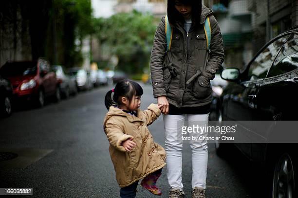 girl walking with mom in a raining day - holding hands in car stockfoto's en -beelden