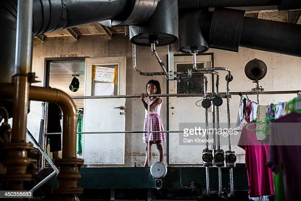 A girl walks across a gantry in the hull of a tanker that ran aground in a particularly badly damaged part of Tacloban on November 18 2013 in Leyte...