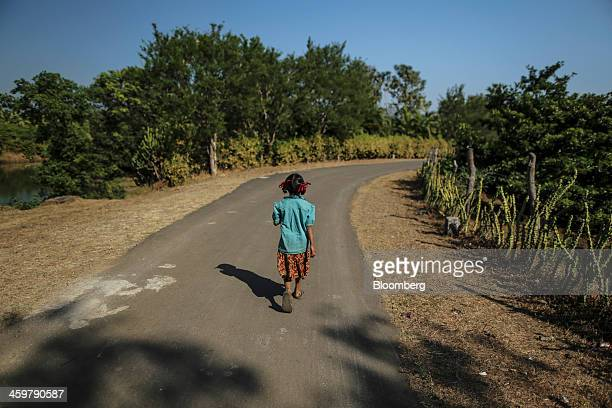 A girl walks along Dahanu Road in Kainad Maharashtra India on Saturday Dec 21 2013 The construction of 600000 kilometers of country roads addition of...