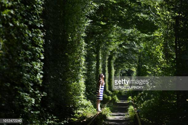 A girl walks along former railway tracks in the socalled 'Tunnel of Love' surrounded by arches of intertwined trees near the Ukrainian village of...