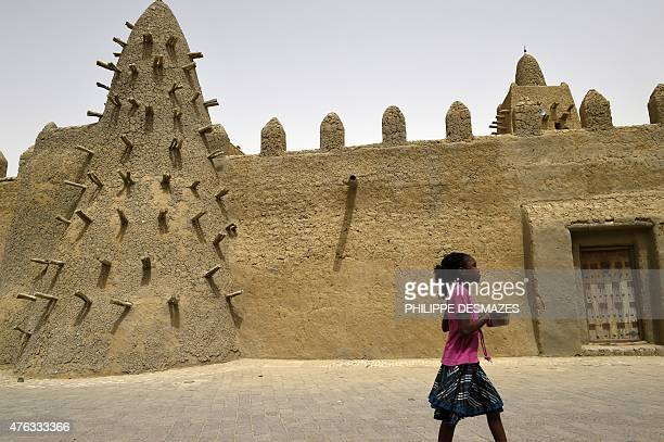 A girl walks along the surrounding wall of the Djingareyber Mosque on June 6 2015 in Timbuktu during the joint operation 'La Madine 3' part of the...