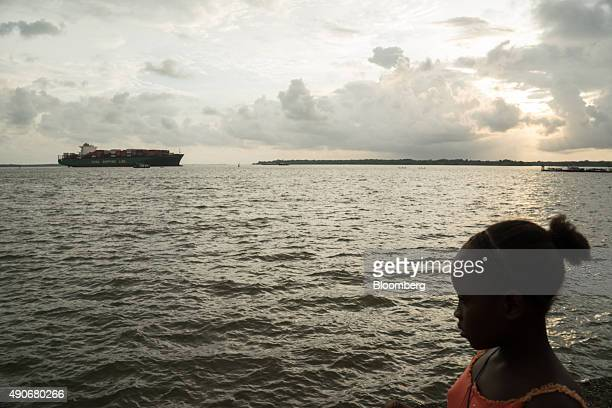 A girl walks along the water's edge as a container ship arrives at the port in Buenaventura Colombia on Friday Sept 18 2015 Buenaventura which serves...