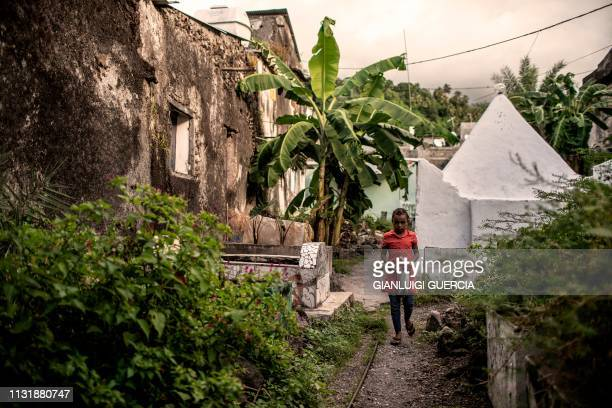 A girl walks by a backyard in the medina of Mutsamudu the capital of Anjouan Island Comoros on March 21 2019 People of Comoros on March 24 will take...