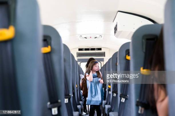 girl walks down bus aisle to exit at her stop - persons with disabilities stock pictures, royalty-free photos & images