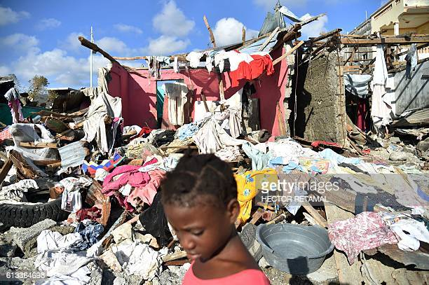 A girl walks in a beach next to the debris left by Hurricane Matthew in Jeremie Haiti on October 8 2016 The full scale of the devastation in...