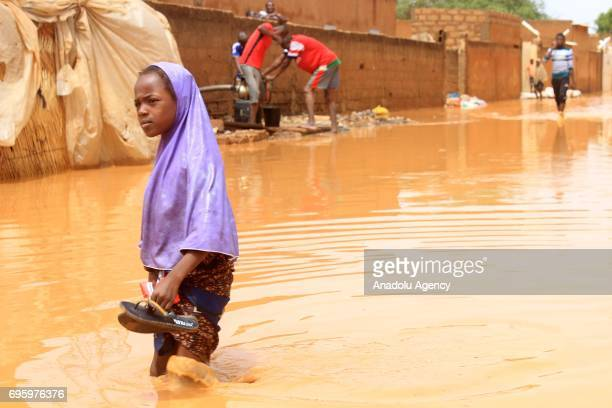 A girl walks in a flooded way after torrential rains at the Saga neighborhood in Niamey Niger on June 14 2017