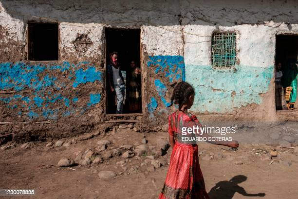 Girl walks in front of a house while a man and a woman look out from a door in the town of Mehoni, Ethiopia, on December 11, 2020. The town of...