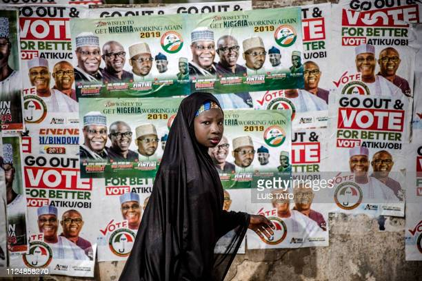 TOPSHOT A girl walks in front of electoral posters in support of the opposition Peoples Democratic Party at Ribadu Square Jimeta Adamawa State...