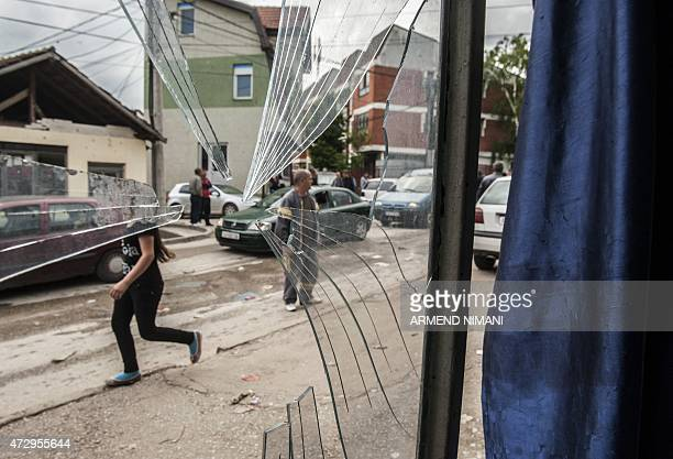A girl walks next to a damaged shop after fighting between Macedonian police and an armed group in the town of Kumanovo on May 11 2015 Shooting broke...