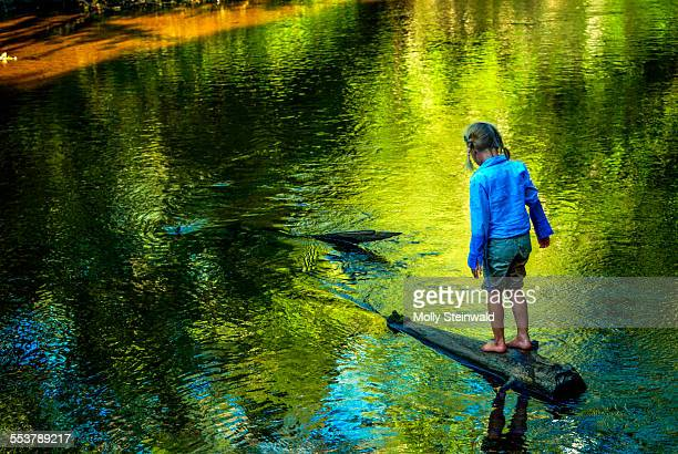 a girl walks on a submerged log near hiawatha national forest mi. - hiawatha national forest stock pictures, royalty-free photos & images